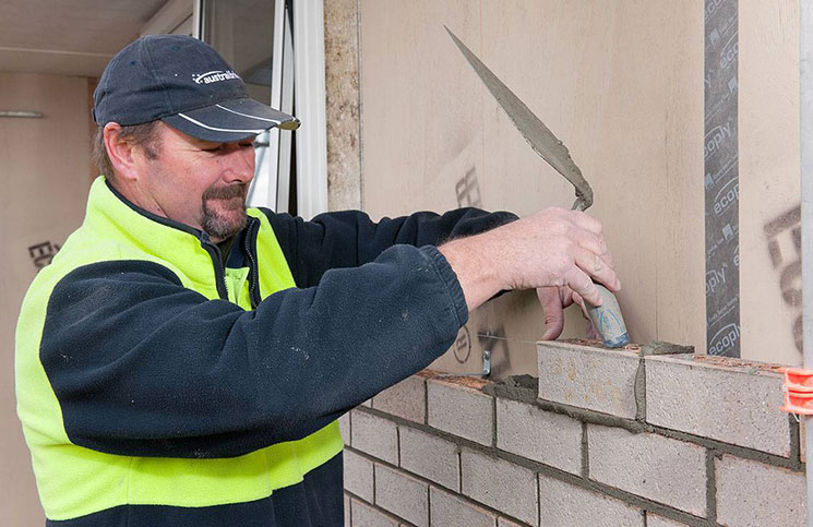 Bricklayer Bernie Caddick laying Austral bricks.